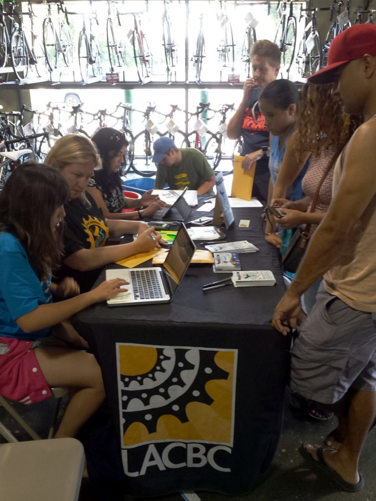 Volunteers sign up LACBC River Ride participants at Performance Bike